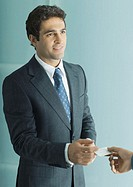 Businessman handing second man business card