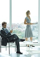 Businessman and woman waiting in lobby, man checking cell phone, woman standing in background, holding magazine