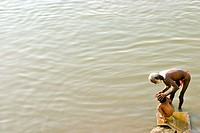 An old man washing his grand-son in the sacred river Ganges in Varanasi