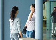 Two young women standing together near cardboard box, one using cell phone and holding laptop