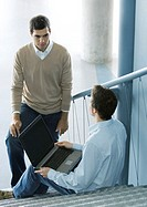 Two male colleagues talking, one sitting on stairs with laptop