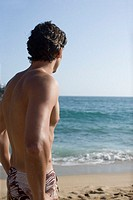 Young adult man looking at the ocean, Rear View, Differential Focus