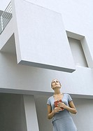 Woman standing in front of building, holding closed book, eyes shut, low angle view