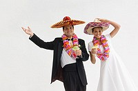 Bride and groom wearing sombreros and leis and holding margarita