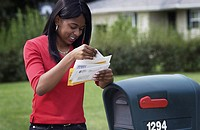 African American woman getting mail from mailbox