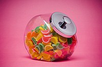 Fruit flavored gummy candy in glass container with metal lid