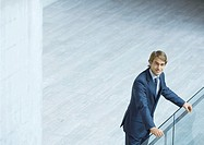 Businessman leaning on railing, high angle view