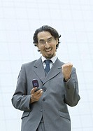 Businessman holding cell phone, making fist and shouting