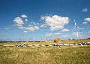 Wind turbine in field with bales of hay, barbed wire in foreground