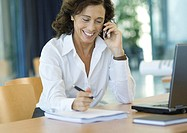 Businesswoman working at desk with cell phone