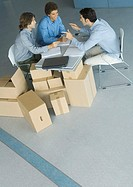 Businessmen sitting at table top supported by cardboard boxes, high angle view