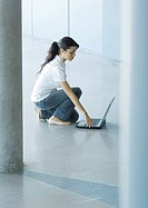 Young woman crouching on floor, using laptop