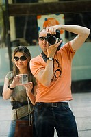 Mid adult man and a young woman taking photographs
