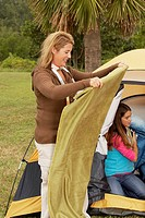 Side profile of a mid adult woman holding a blanket with her daughter near a tent