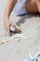 Girl holding a conch shell and playing with a starfish on the beach