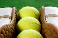 Close-up of a pair of tennis shoes with three tennis balls