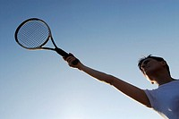 Low angle view of a mid adult woman holding a tennis racket