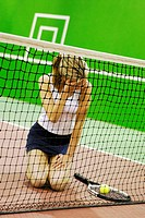 Close-up of a young woman kneeling on a tennis court