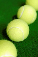 High angle view of four tennis balls in a row