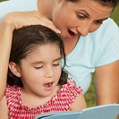 Close-up of a girl and her mother reading a book