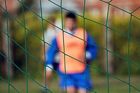 Two soccer players in front of a net