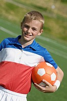 Portrait of a soccer player holding a soccer ball and smiling
