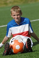 Portrait of a soccer player sitting with a soccer ball