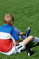 Rear view of a soccer player tying his shoelaces