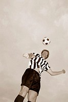 Low angle view of a soccer player heading a soccer ball