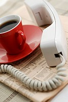 Close-up of a cup of black tea with a telephone receiver on a newspaper