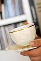 Close-up of a person's hand holding a cup of tea and a saucer