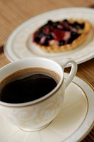 Close-up of a cup of black tea with a tart