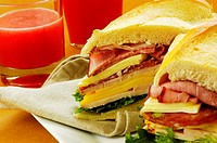 Close-up of roast beef and cheese sandwich near a glass of fruit juice