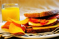 Close-up of orange juice with a sandwich and potato chips