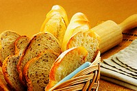 Close-up of bread in a basket and a roller pin on a place mat