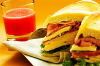 Close-up of roast beef and cheese sandwiches near a glass of fruit juice