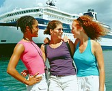 Close-up of three young women standing on the beach in front of a cruise ship, Bermuda
