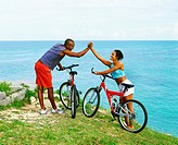 Side profile of a young couple holding hands near bicycles, Bermuda