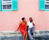 Young couple sitting in front of a house and talking on a mobile phone, Bermuda