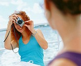 Close-up of a young woman taking a photograph of another woman, Bermuda