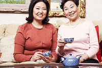 Portrait of a daughter and her mother holding tea cups