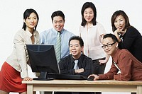 Portrait of a group of business executives smiling in front of a computer