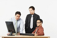 Three businessmen looking at a computer monitor