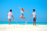 Two men swinging jumprope for woman on beach