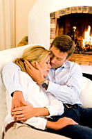 Couple hugging on sofa with eyes closed