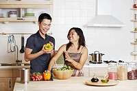 Close-up of a young man and a young woman standing and holding yellow bell peppers