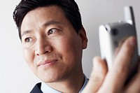 Close-up of a businessman holding a mobile phone thinking