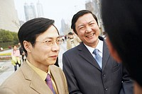Close-up of two businessmen smiling