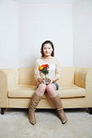 Portrait of a young woman sitting on a couch holding a flower pot