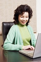 Close-up of a businesswoman using a laptop smiling